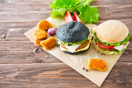 Delicious fast food. Two hamburgers with beef burger cutlet, fried onion, spinach, ketchup sauce and blue cheese in traditional buns, served on wood chopping board over dark wooden background. 版權商用圖片
