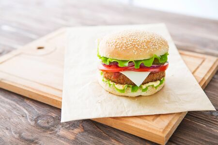 Delicious fast food. Homemade hamburger. Large. Homemade, beef hamburger with cheese and vegetables. 版權商用圖片