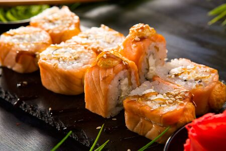 Set of baked sushi rolls with wasabi and ginger on a black background. Japanese oriental cuisine