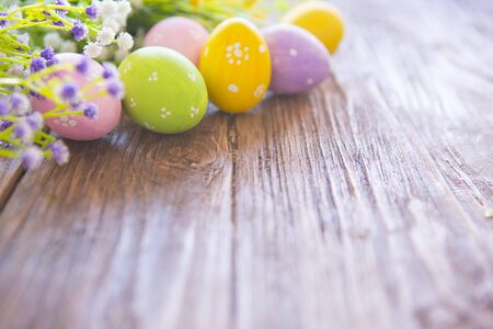 Easter eggs with wildflowers on a brown wooden background. Reklamní fotografie