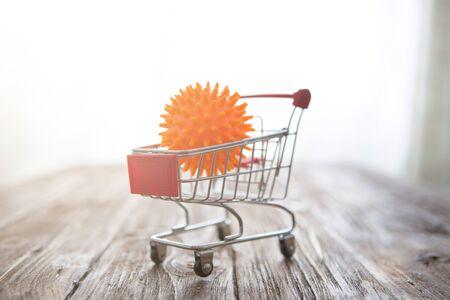Impact of coronavirus COVID-19 on the global economy, Abstract virus strain orange model of Coronavirus disease COVID-19 in a shopping cart on wooden table. Financial crisis 2020.