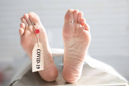 Legs of a corpse in a morgue on a table with a tag with the inscription COVID-19. Pandemic of the new coronavirus. Tragedy and death