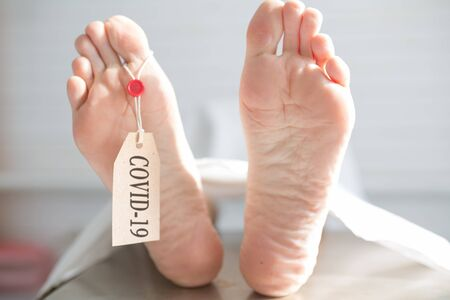 Legs of a corpse in a morgue on a table with a tag with the inscription COVID-19. Pandemic of the new coronavirus. Tragedy and death . Virus Pandemic Protection Concept 스톡 콘텐츠
