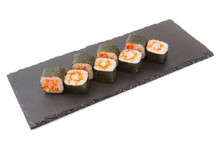 Sushi rolls on black slate on white background.