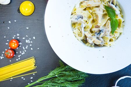 Pasta with mushrooms on a black slate background. Banque d'images