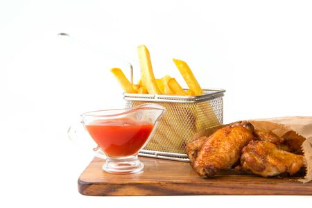 Grilled meat assortment with french fries served on wooden board isolated at the white background.