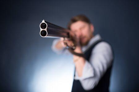 Manager holding a shotgun on dark blue background.