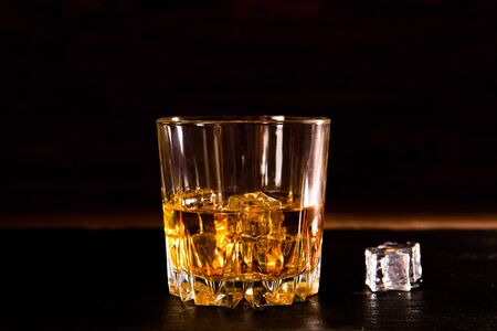 Whiskey drink on wooden table over dark background.