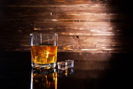 Glass of whiskey with ice cubes on a black table against wooden background