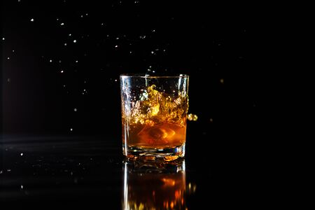 Ice cube falls into a glass with whiskey on black background. Fluid in motion. Droplets of spray. Stok Fotoğraf