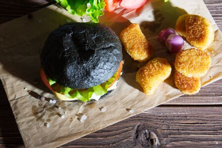 Delicious fast food. Cheeseburger with a black bun on a kraft paper on wooden Board
