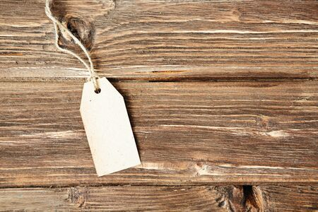 Blank tag on wooden background One paper blank tags with rope on wooden background. 스톡 콘텐츠