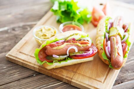 Delicious fast food. Tasty hot dogs on wooden background Stockfoto