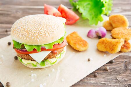Delicious fast food. Homemade hamburger. Large. Homemade, beef hamburger with cheese and vegetables. Stockfoto