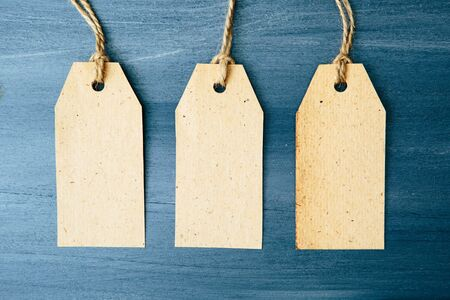 Three brown blank paper price tags or labels set hanging on a rope on the blue wooden background. Three paper empty tags with rope on wooden background.