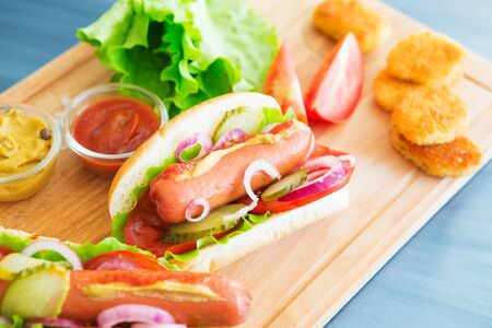 Delicious fast food. Hot dogs with vegetables on wooden table