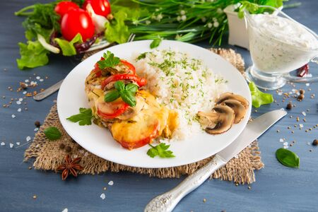 Chicken fillet baked in cheese with rice and vegetables. Wooden background. Фото со стока