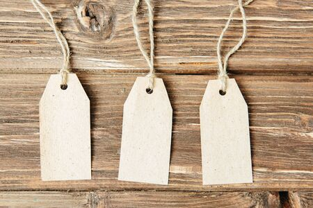 Paper hang on clothesline Three paper empty tags with rope on wooden background.
