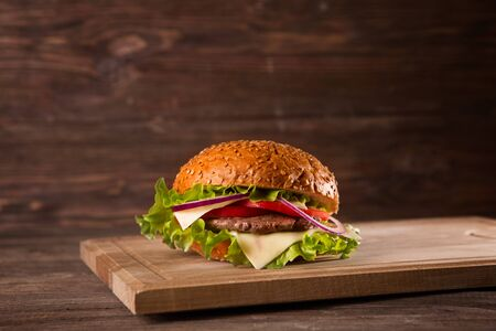 Burger on a wooden board on wooden table over dark background.