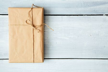 Overhead view of a single holiday package wrapped with eco friendly craft paper and tied with twine. Square format on a rustic wooden table.