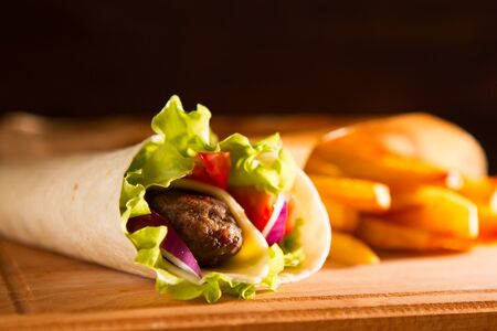 Tasty fresh wrap sandwich with beef and vegetables, on wood table.