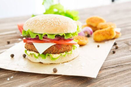 Delicious fast food. Homemade hamburger with lettuce, tomato, cheese and cucumber on a cutting board Stockfoto