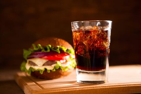 fresh big burger and glass cola on wooden table fast food concept.