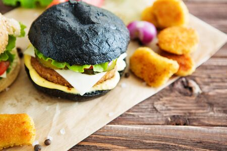 Delicious fast food. Cheeseburger with a black bun on a kraft paper on wooden Board, Close up homemade Japanese Burger