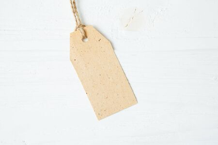 Label tag blank on wooden One paper blank tags with rope on wooden background.