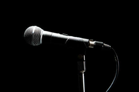 Black modern microphone on stand, black dark background. Accentuated shapes with light. Music and concert concept.