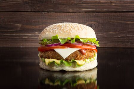 Delicious fast food. Delicious tasty burger with lettuce, cheese, onion and tomato on a rustic wooden plank on a black background Stockfoto