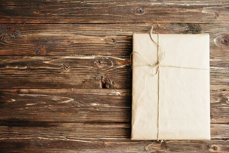 Parcel box wrapped by brown craft paper. On wooden background. Delivery service.