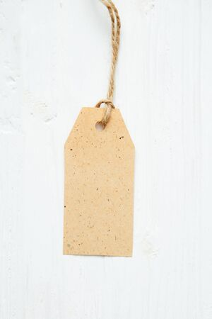 price tag label on wooden background One paper blank tags with rope on wooden background. 스톡 콘텐츠 - 150546070