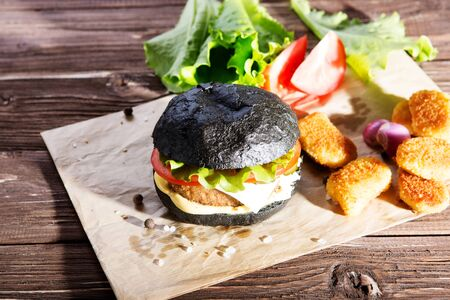 Delicious fast food. Tasty burger with bacon on table against black background. Space for text