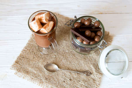 Delicious chocolate smoothie with marshmallows on white table.