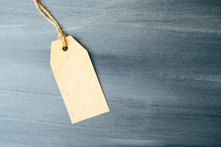 Paper tag on wooden background One paper blank tags with rope on wooden background.