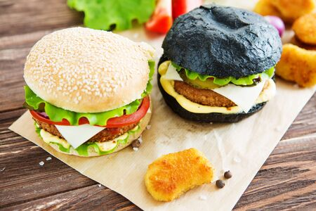 Delicious fast food. Delicious hamburgers on wooden background