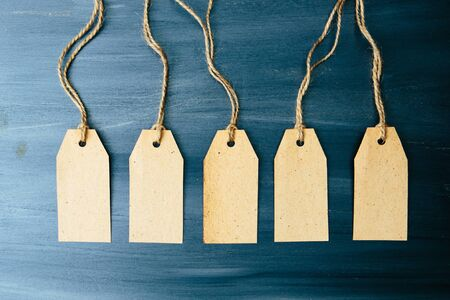 Five brown blank paper price tags or labels set hanging on a rope on the blue wooden background.