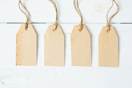 Four blank cardboard labels over brown wooden background. Four paper blank tags with rope on wooden background. 스톡 콘텐츠 - 150551291