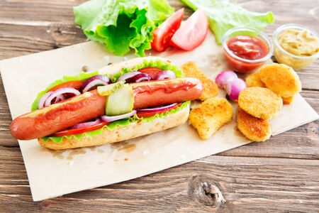 Delicious fast food. Hot dog with sausage, cucumber, tomato and lettuce on dark wooden background. Summer hotdog.