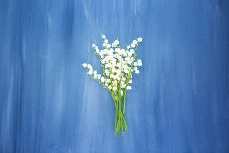 Wonderful fragrant white flowers with a delicate scent. Lily of the valley flowers on gray wooden or metal table Copy space.