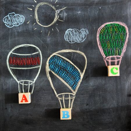 Back to school. Drawing of three balloons or aerostats on a school blackboard with the letters ABC and school supplies.