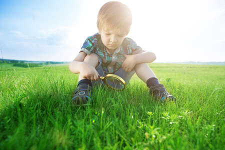 Get to know the world. Everything is incredible near you. Young boy exploring nature in a meadow with a magnifying glass looking at a grass