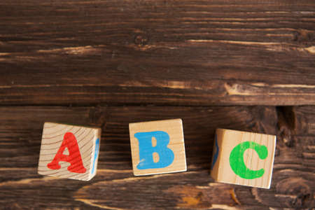 Cubes with letters ABC on rustic wooden table