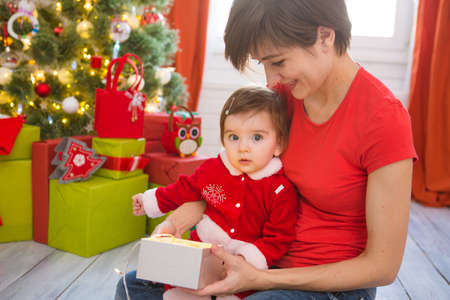 Young mother and her little daughter dressed as santa claus opening a magical Christmas gift by a Christmas tree in cozy living room in winter