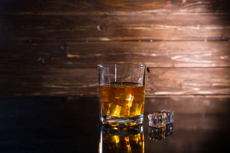 Glasss of whiskey with ice cubes on dark wooden background Stock Photo