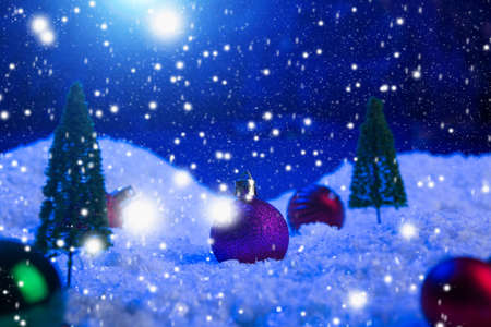 Christmas background with Christmas balls on snow over fir-tree, night sky and moon. Shallow depth of field. Christmas background. Fairy tale. Macro. Artificial magic dreamy world.