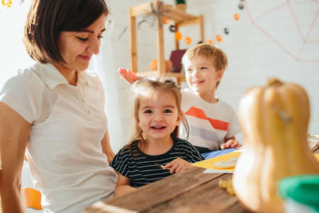 Happy Halloween. Attractive young woman with her little cute kids are preparing to Halloween on kitchen having fun with pumpkins. Happy Halloween concept