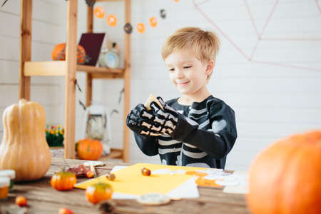Halloween party. Little boy in a skeleton costume is ready to celebrate Halloween. Boy in a halloween dress-up room.