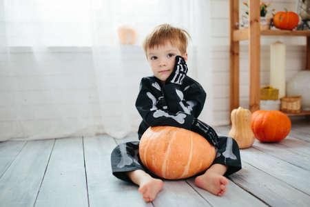Portrait of a little boy in a skeleton costume is ready to celebrate Halloween. Boy in a halloween dress-up room.
